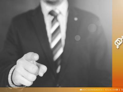 hombre con traje señalando a la cámara con el dedo, junto al símbolo de los dos géneros